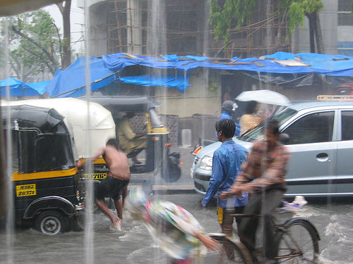 Children play in the water as traffic comes to a halt in Mumbai.